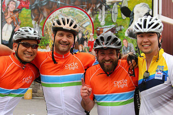 Four male adult riders wearing Cycle for Sight jerseys and bicycle helmets. One rider has a beard and is holding up his index finger in a number one gesture. The man on the far left is wearing sunglasses.