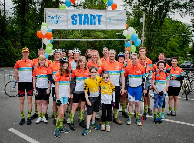 Group photo of cyclers. A start banner hangs in the background.