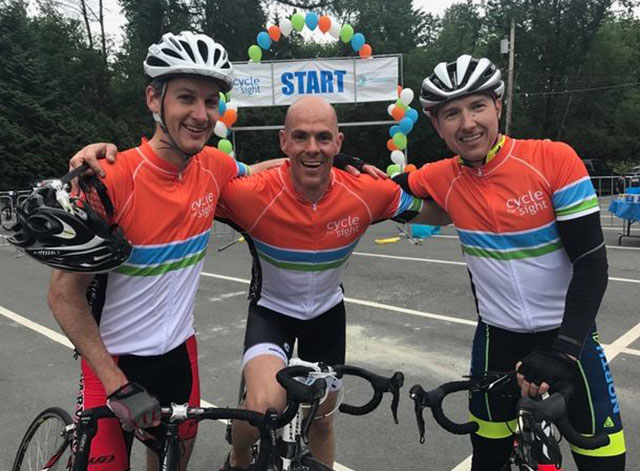 Photo of three male cyclers smiling. They are wearing cycle for sight jerseys.
