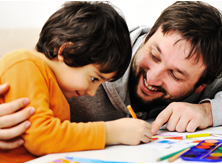 A father with a smile looks upon his son colouring on a piece of paper.
