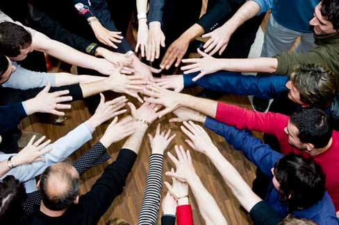 Ten people put their hands in the middle of a circle.