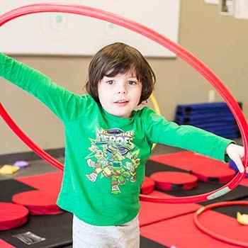 Boy plays with a hoola hoop.